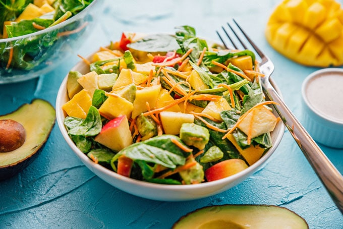 Avocado mango salad with spinach, mango, carrots, and apple in a bowl on a blue background