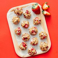 Strawberry oat cookies on a wooden plate with a red background