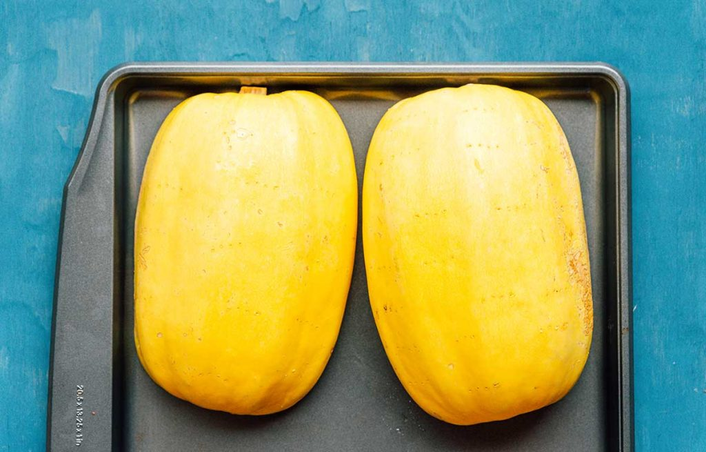 Two halves of a spaghetti squash sitting face-down on a baking sheet