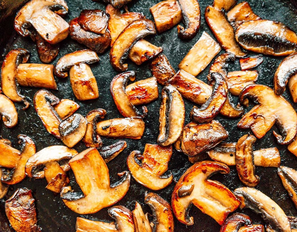 A saute pan filled with sliced mushrooms