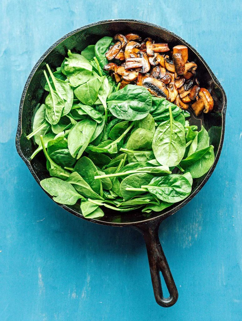 A saute pan filled with mushrooms and spinach