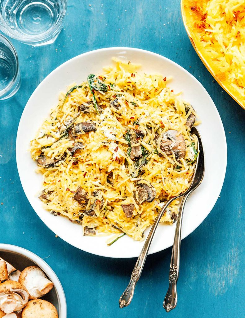 A dish filled with spaghetti squash with mushrooms, spinach, and goat cheese