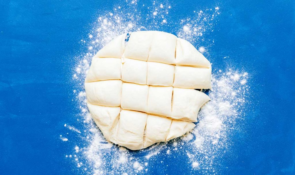 Cutting dough into pieces on a blue background