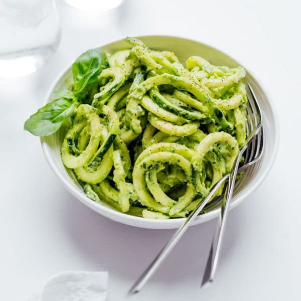 This spiralized zucchini pasta is tossed in creamy basil and avocado pesto to make a deliciously low carb and gluten-free dinner!