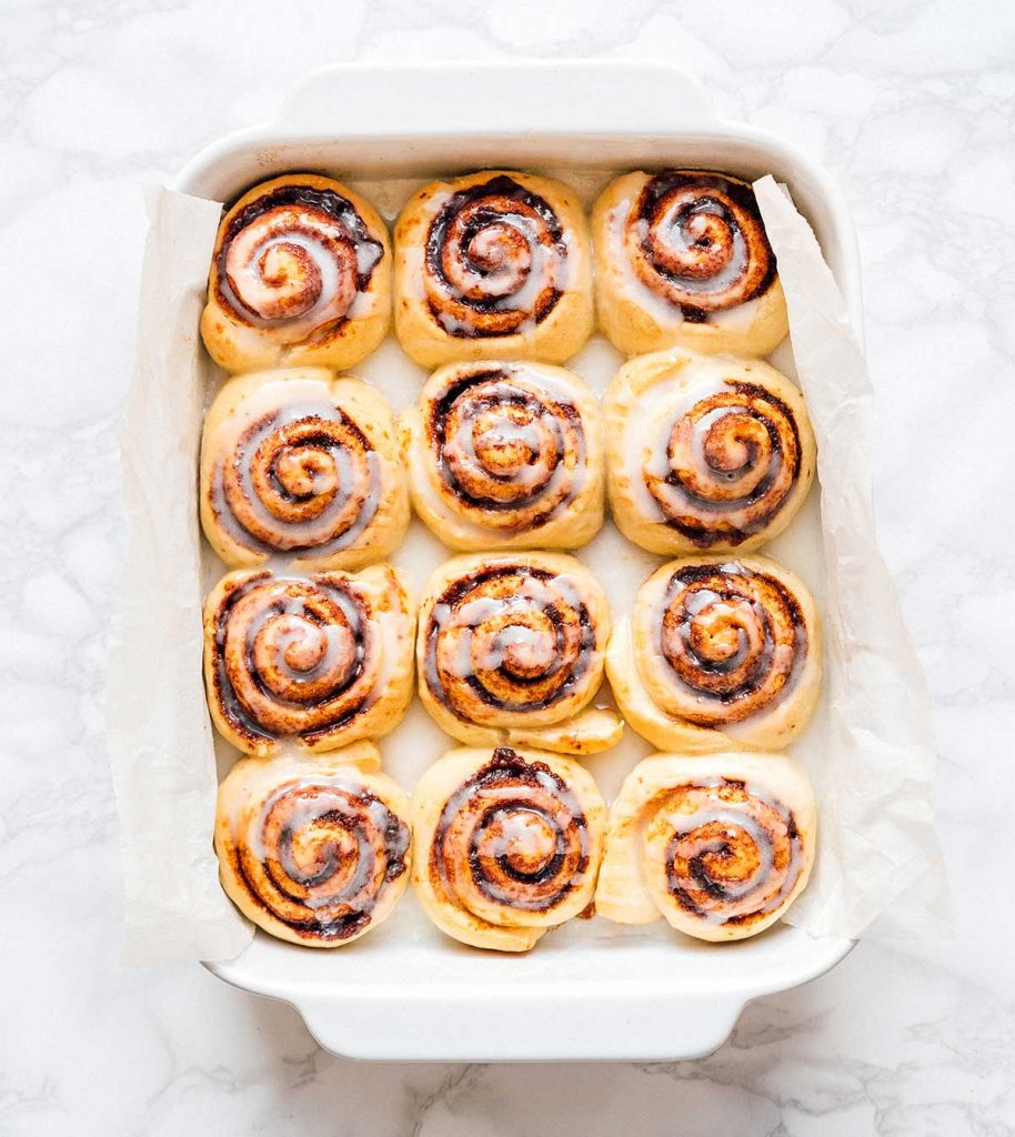Baked cinnamon rolls in a baking dish on a marble background