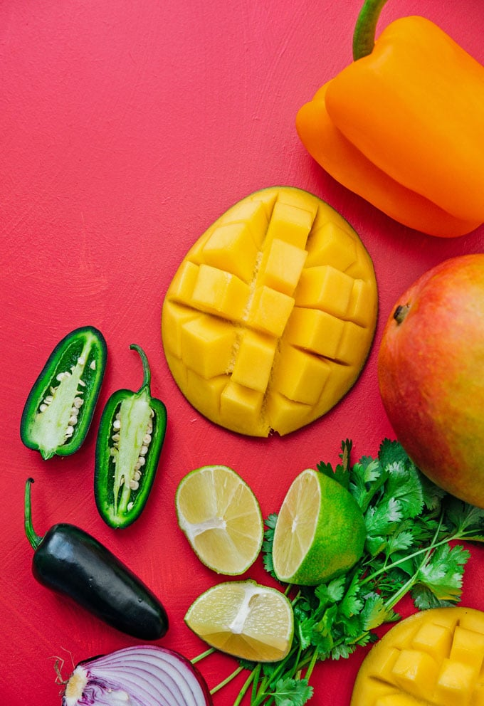 Ingredients to make mango salsa, mango, jalapeno, cilantro, lime, pepper