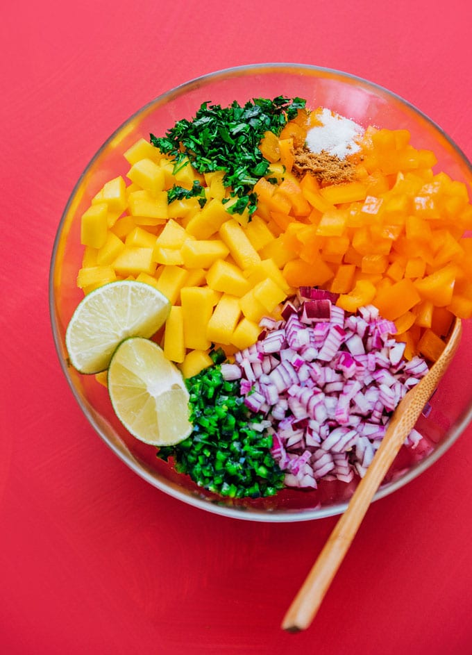Ingredients to make mango salsa in a glass bowl
