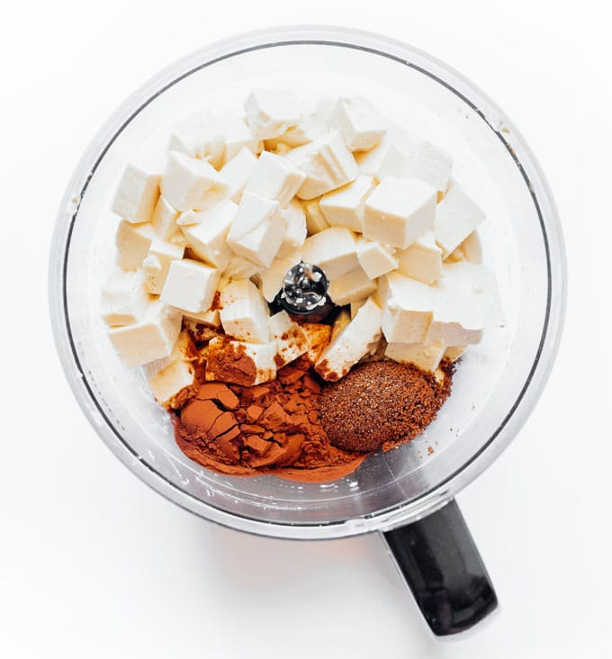 Ingredients to make vegan tofu chocolate mousse in a food processor