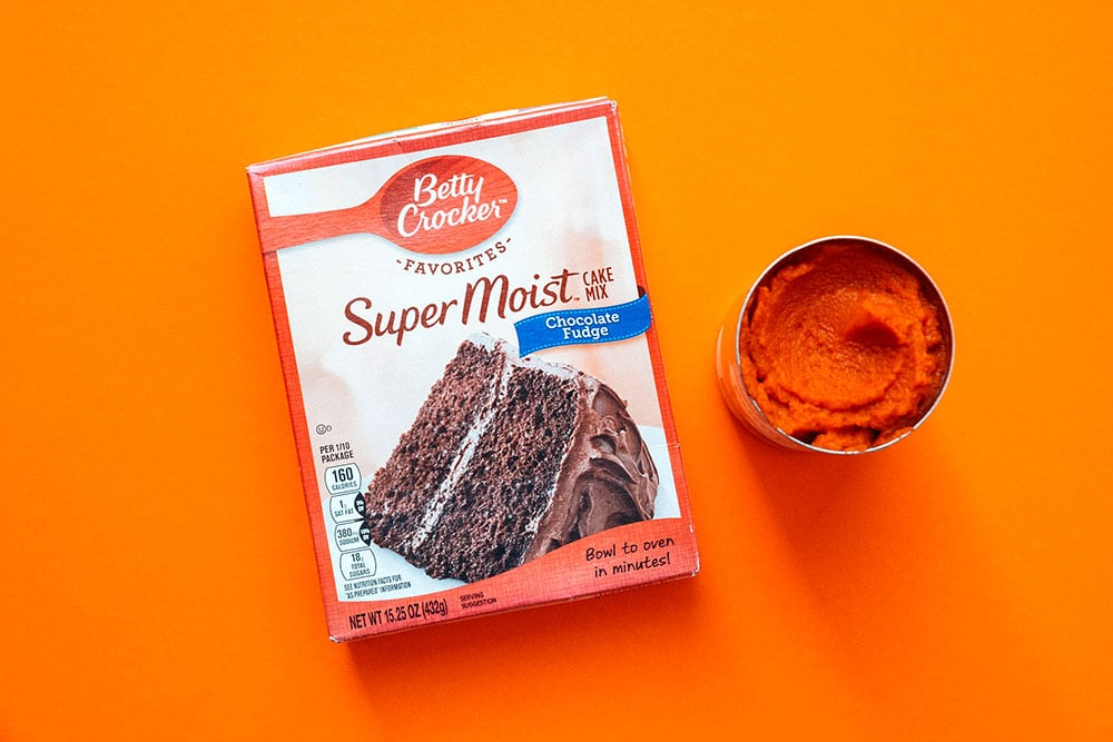 Can of pumpkin and chocolate cake mix on an orange background