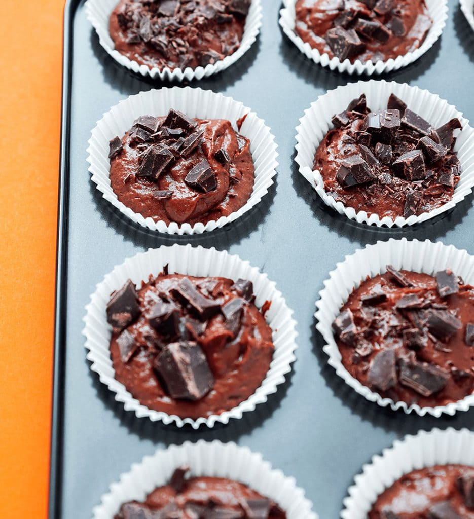 Healthy chocolate cupcakes in a muffin tin on an orange background