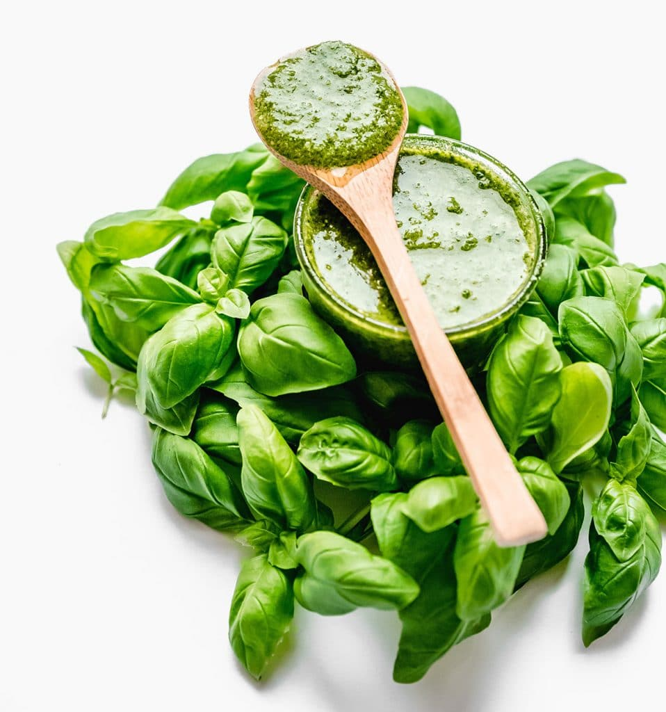 Homemade pesto in a glass jar with basil leaves