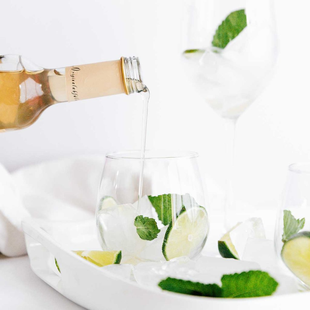 Pouring elderflower syrup into a hugo spritz cocktail in a glass with lime and mint