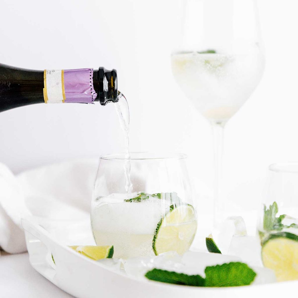 Pouring prosecco into a hugo spritz cocktail in a glass with lime and mint