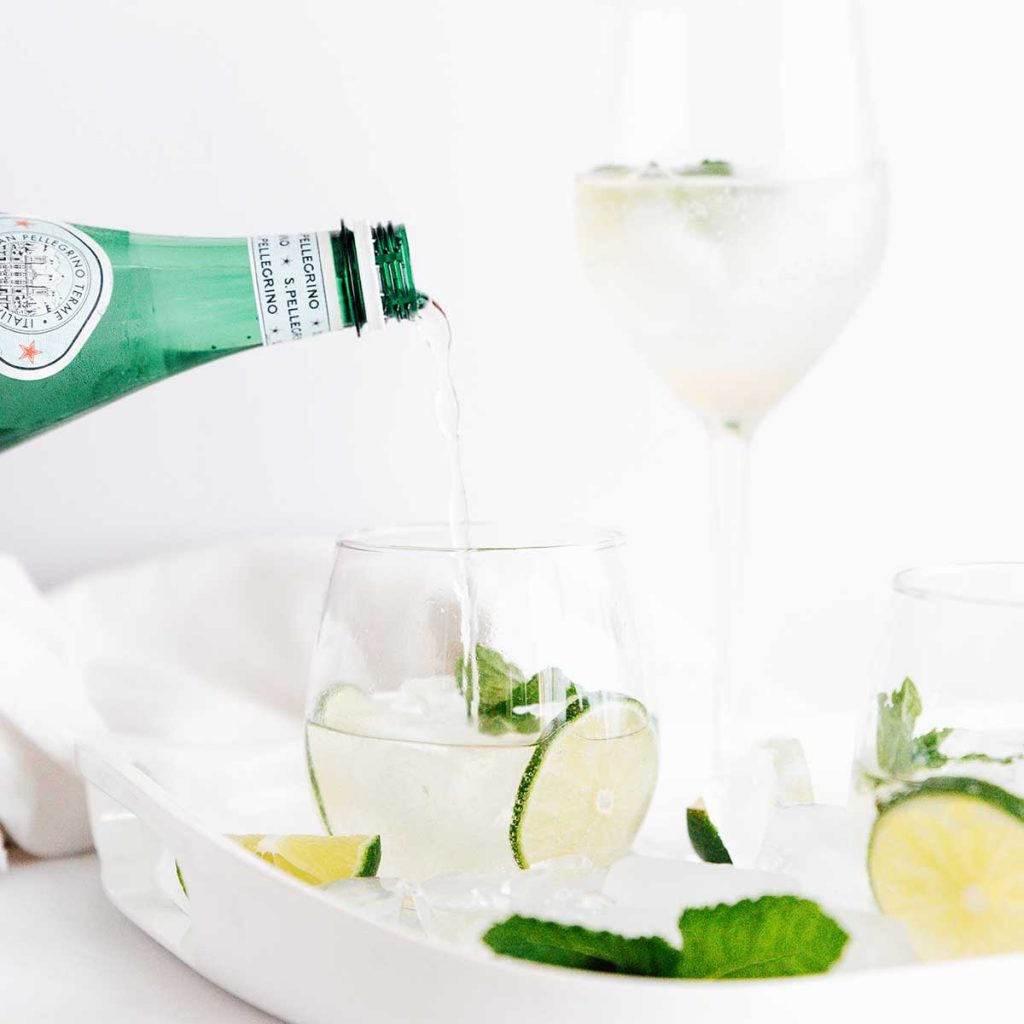 Pouring sparkling water into a hugo spritz cocktail in a glass with lime and mint
