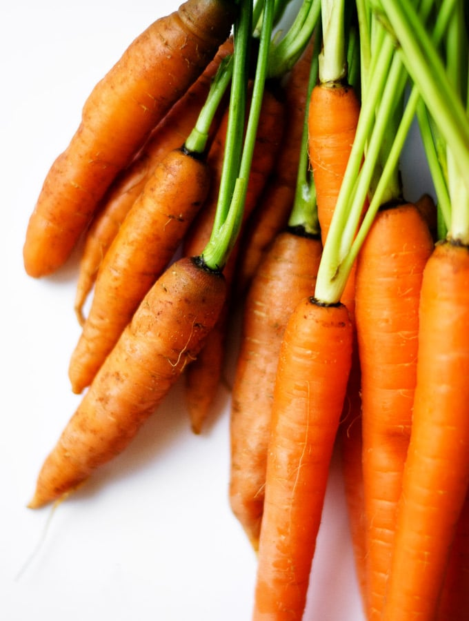 Close-up photo of a bundle of carrots on a white background