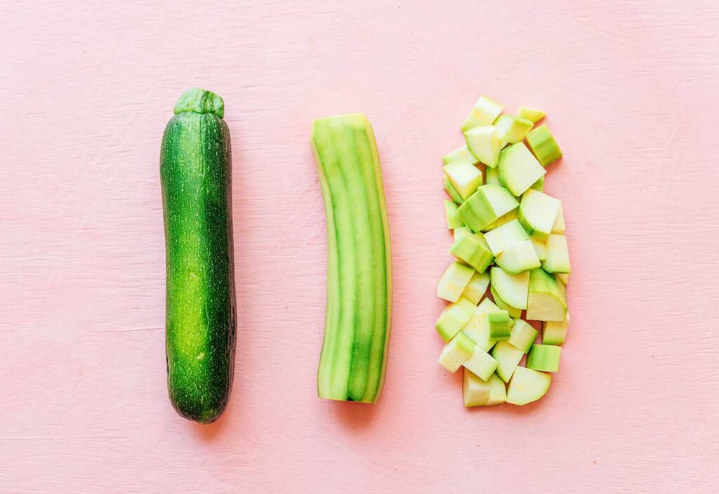 Three zucchinis lined up on a pink background displaying how they should be cut for zucchini crisp - whole, peeled, and diced