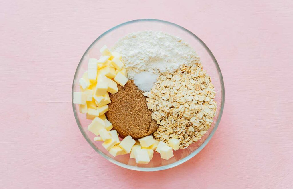 A clear glass bowl filled with cubed butter, flour, sugar, brown sugar, and oats