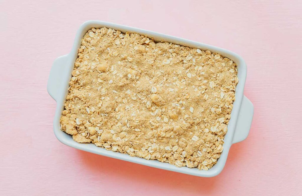 A casserole dish filled with a layer of zucchini crisp crumble topping