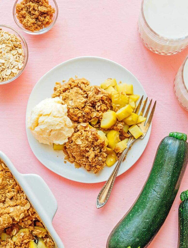 A white plate filled with zucchini crisp and vanilla ice cream