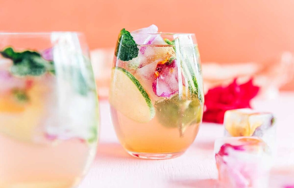 A wine glass filled with a drink and garnished with cucumbers, basil, and edible flower ice cubes