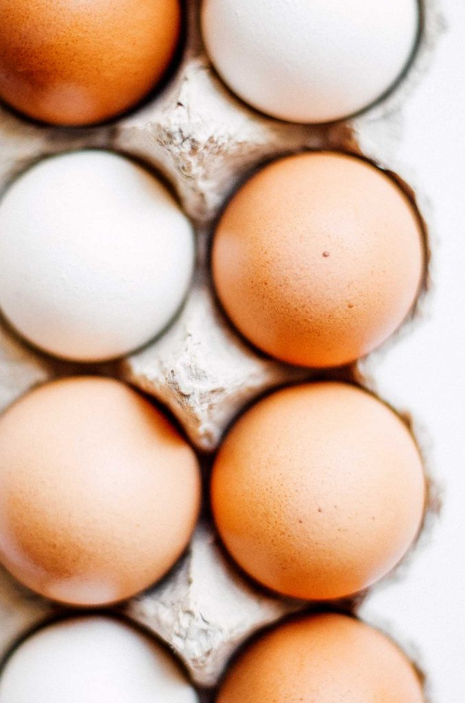 White and brown eggs in a carton on a white background