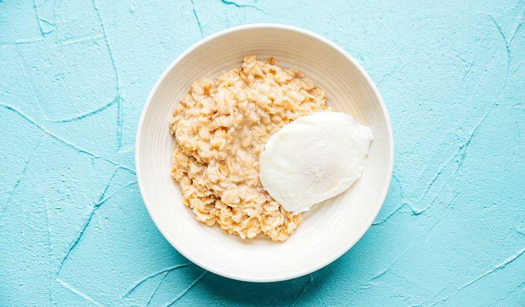 Oatmeal with an egg in a white bowl on a blue background