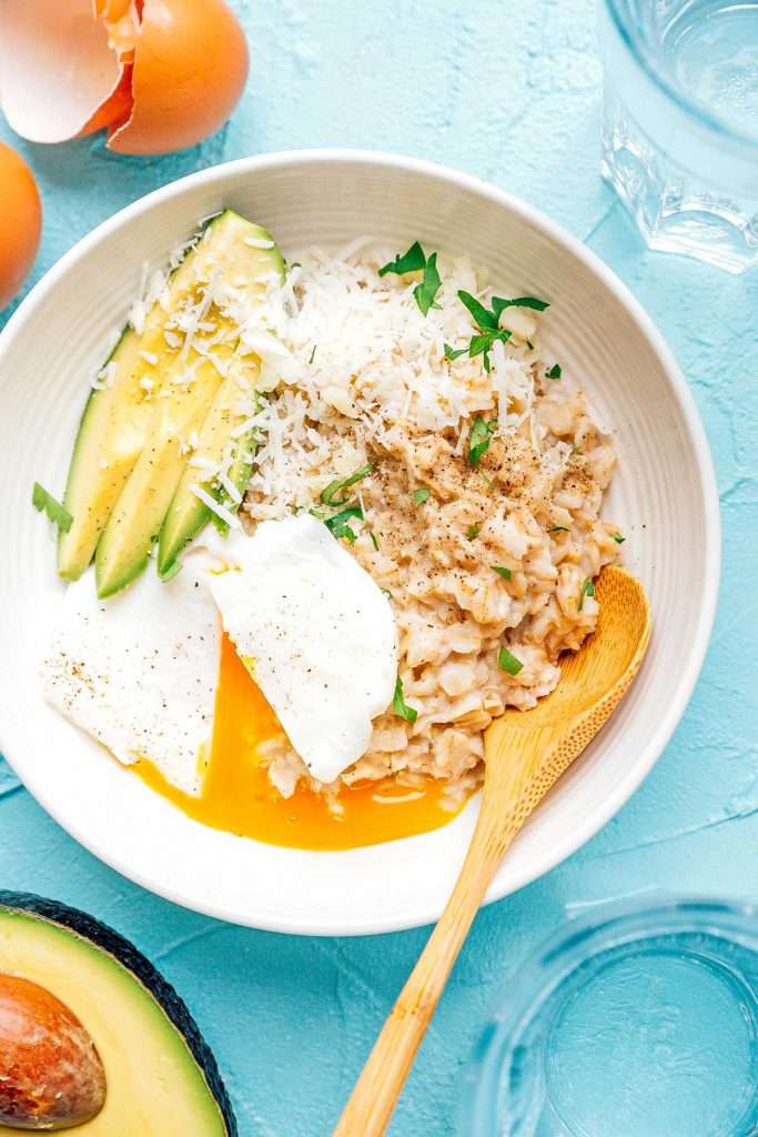 Savory oatmeal with egg and avocado in a white bowl on a blue background