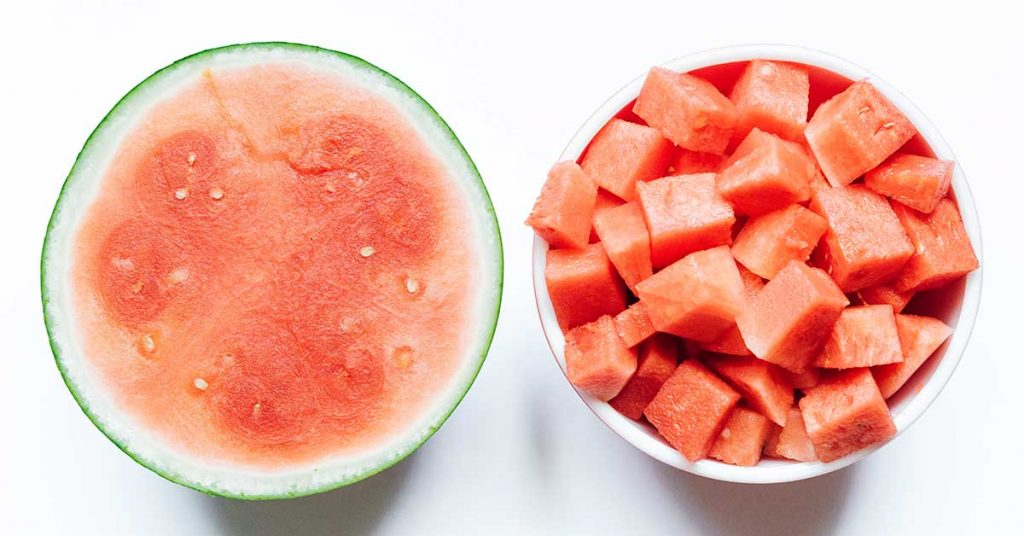 Half a watermelon with cubed watermelon on a white background