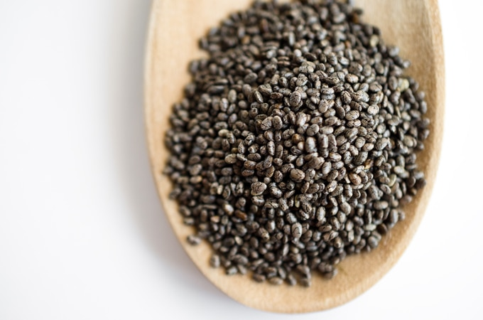 Photo of chia seeds on a wooden spoon with a white background