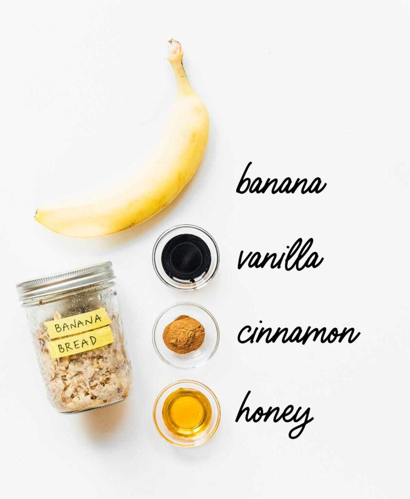A jar of banana bread overnight oats next to a banana, vanilla, cinnamon, and honey