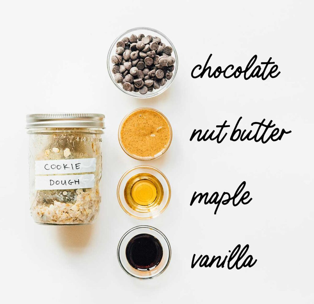 A jar of cookie dough overnight oats laid out next to chocolate chips, nut butter, maple syrup, and vanilla