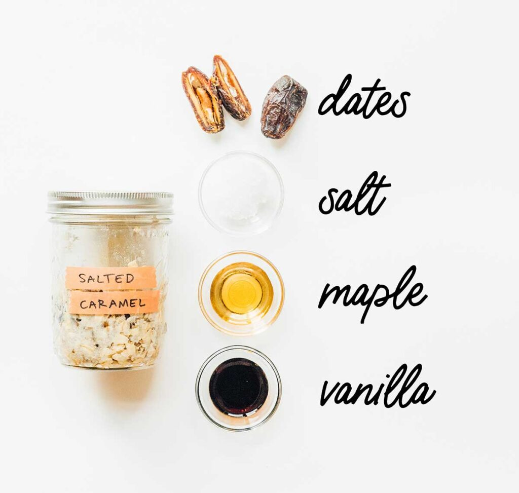 A jar of salted caramel overnight oats laid out next to dates, salt, maple syrup, and vanilla