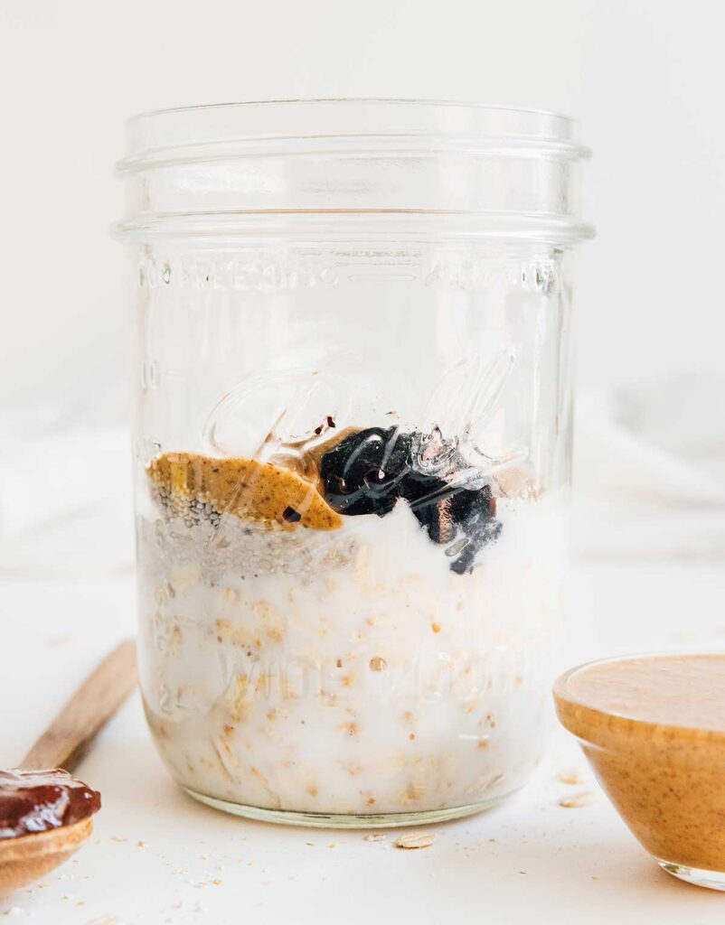 A mason jar filled with pb&j overnight oats ingredients