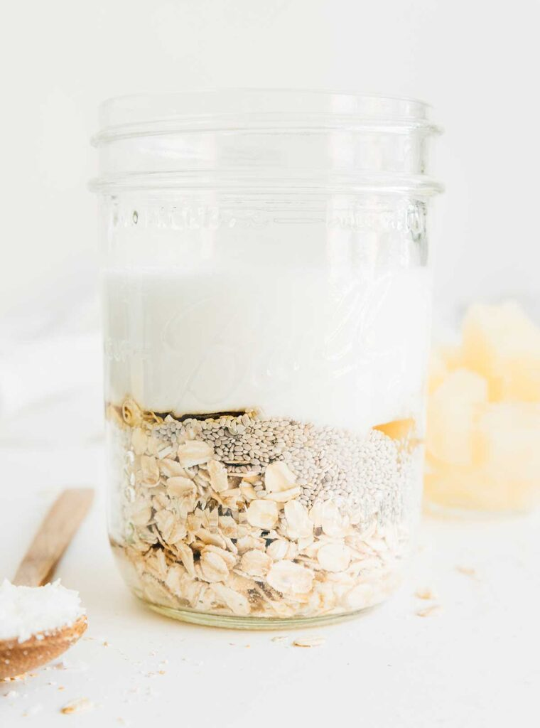 A mason jar filled with piña colada overnight oats ingredients