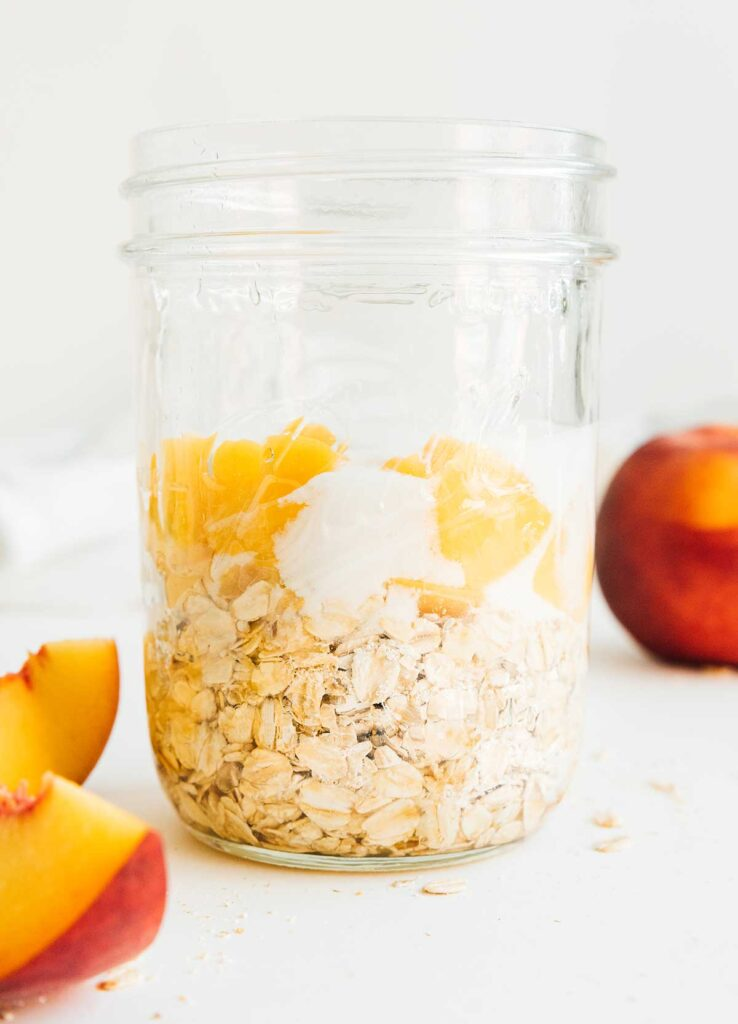 A mason jar filled with peaches and cream overnight oats ingredients