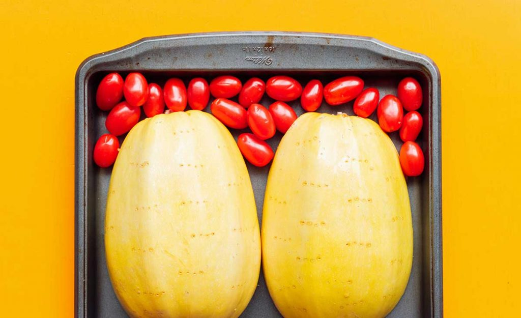 Two spaghetti squash halves placed face-down and 2 cups of cherry tomatoes on a baking sheet