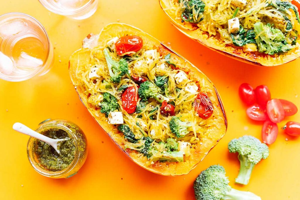 A completed pesto spaghetti squash bowl filled with squash noodles, spinach, broccoli, tomatoes, feta, and pesto