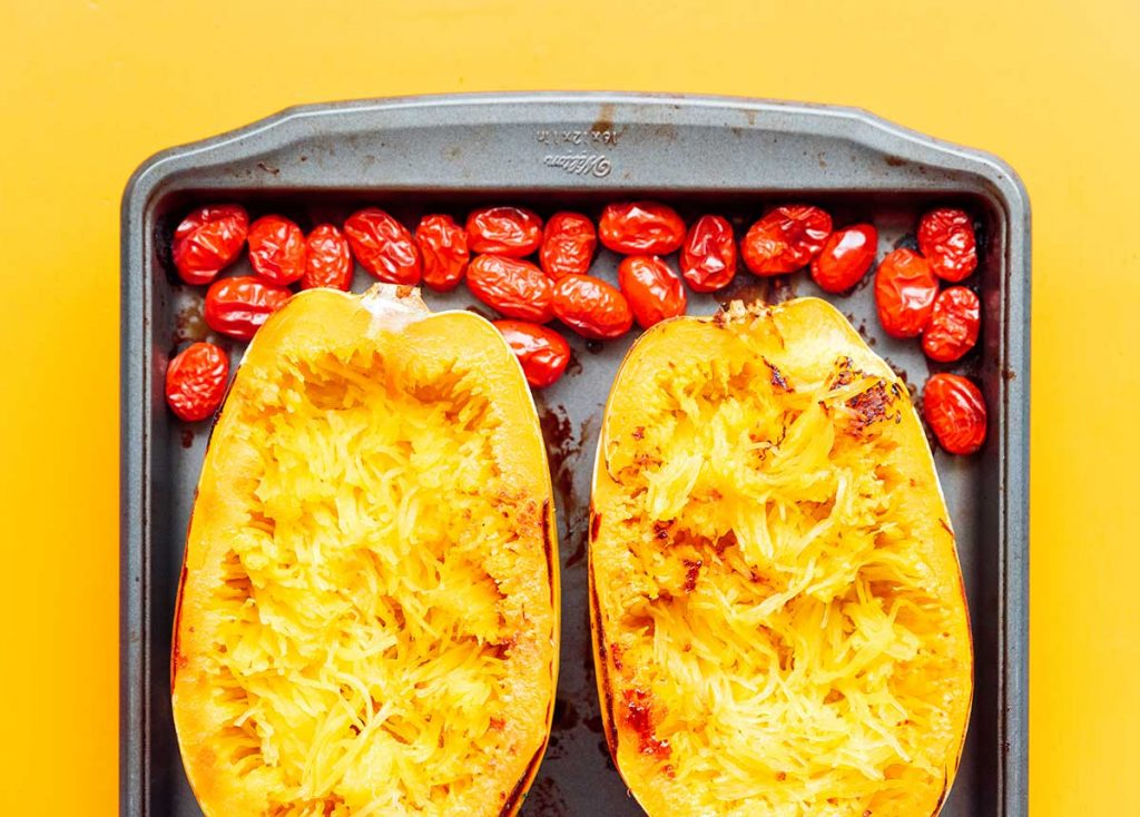 Two halves of a roasted spaghetti squash and two cups of roasted cherry tomatoes on a baking sheet