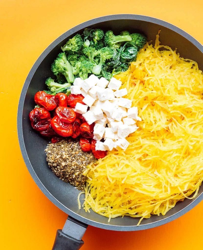 Spinach, broccoli, feta, cherry tomatoes, pesto, and spaghetti squash noodles in a sauté pan