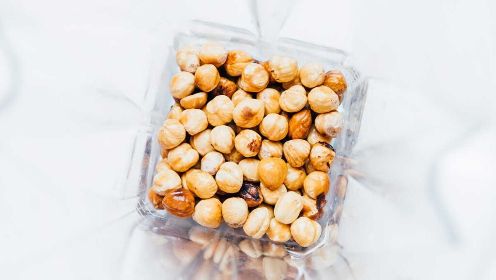 A food processor filled with whole hazelnuts