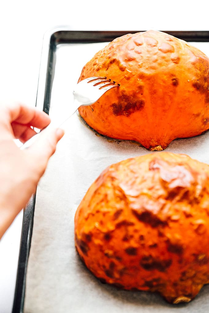 Pumpkin halves on a baking sheet being poked with a fork