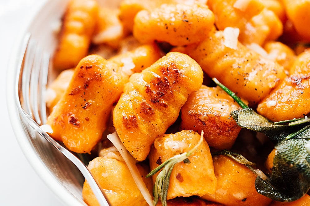 Closeup photo of sweet potato gnocchi in a bowl on a white background