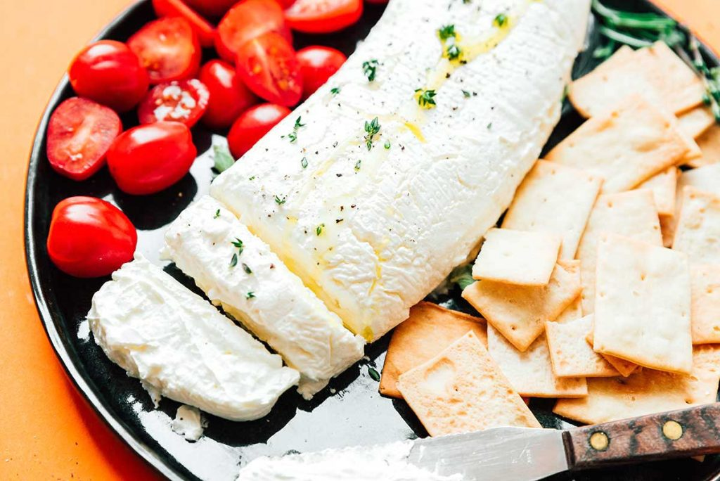 Greek yogurt cheese on a plate with crackers and tomatoes