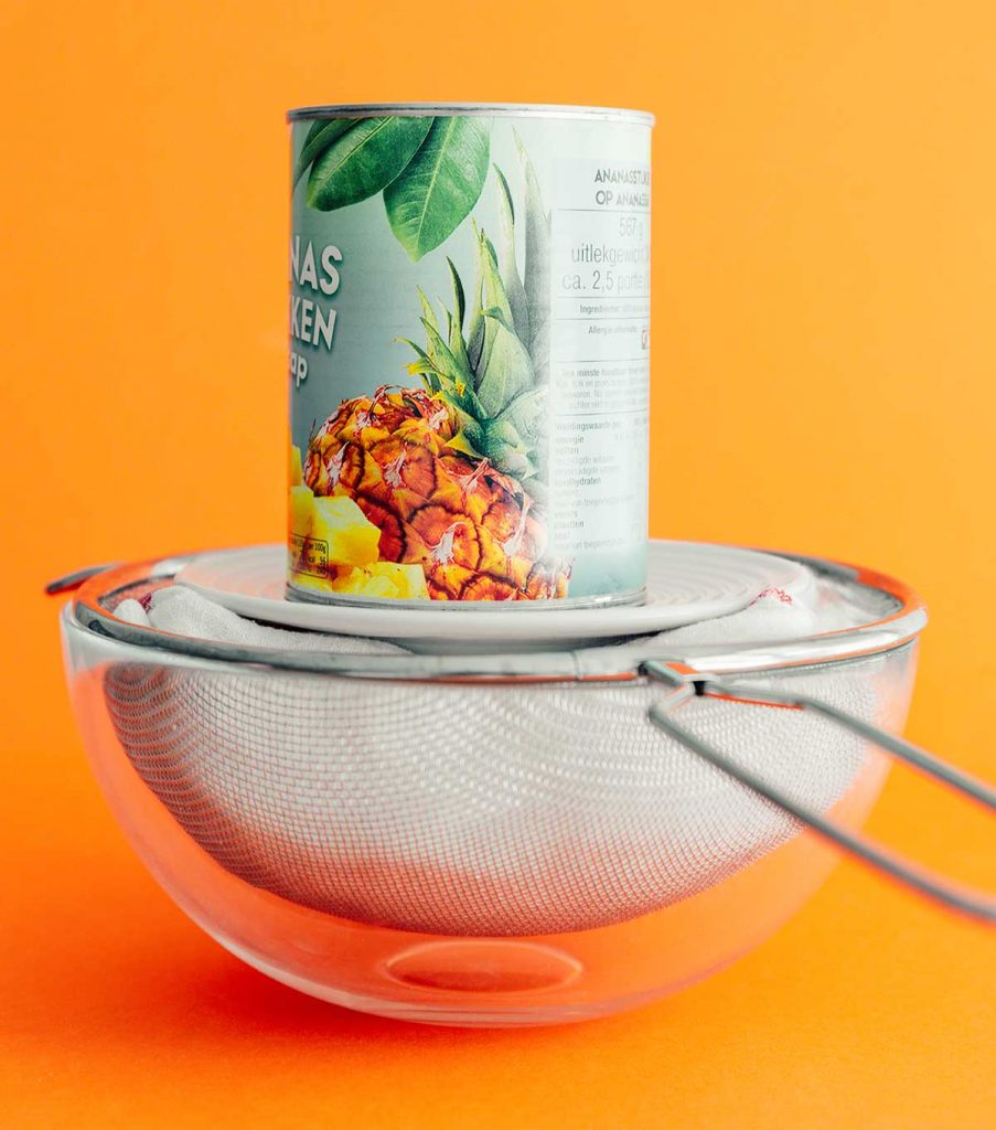 Pressing Greek yogurt cheese in a bowl with a can