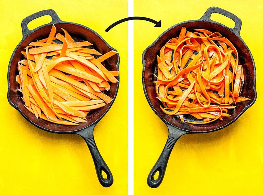 Sweet potato fettuccine noodles in a cast iron skillet on a yellow background