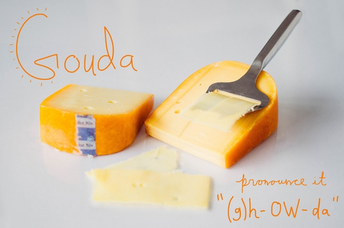 Block of Gouda cheese in the rind being cut with a cheese peeler