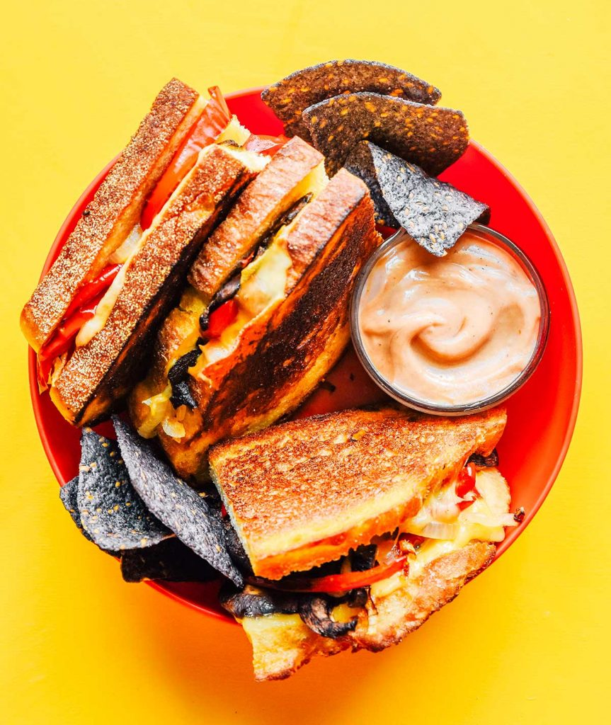 A plate filled with three roasted vegetable paninis, toasty sauce, and tortilla chips