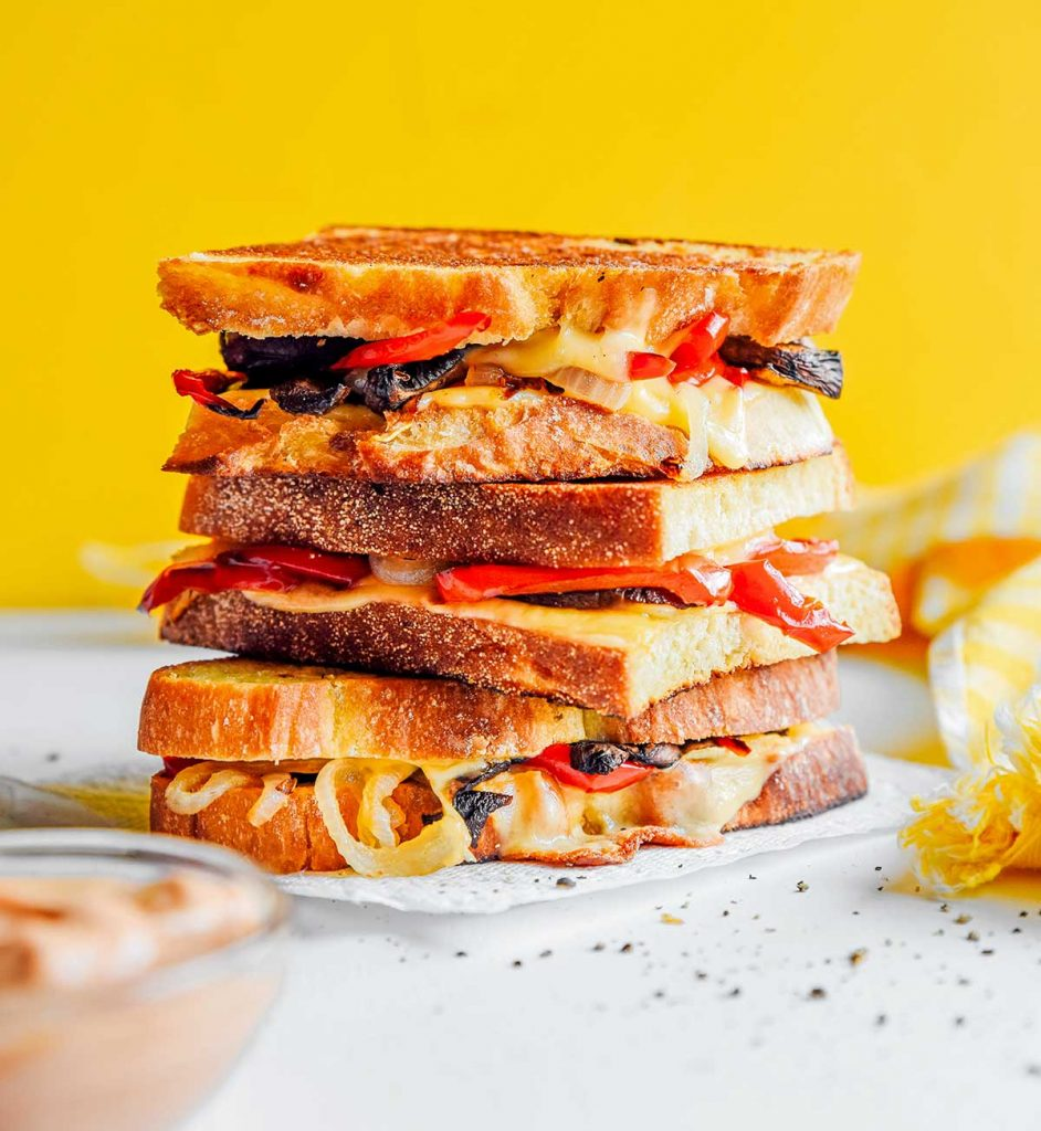 Three roasted vegetable grilled cheeses stacked on top of one another