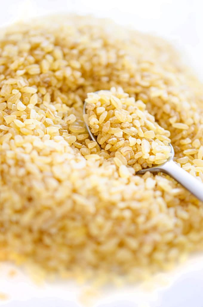 Closeup photo of bulgur grains and a spoon - Everything you need to know about cooking with bulgur, an ancient whole wheat grain that's packed with protein, fiber, and vitamins!