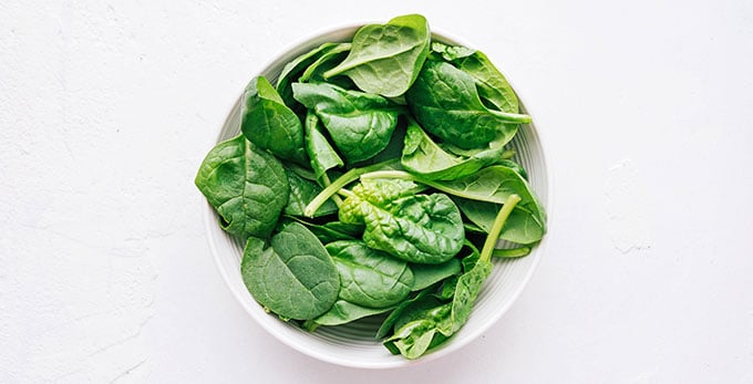 Spinach in a bowl on a white background